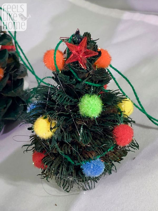 A close up of a pine cone Christmas tree with pompoms for ornaments