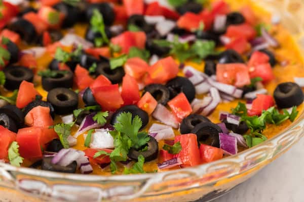 up close healthy taco dip with diced tomatoes, black olives, onion, and cilantro