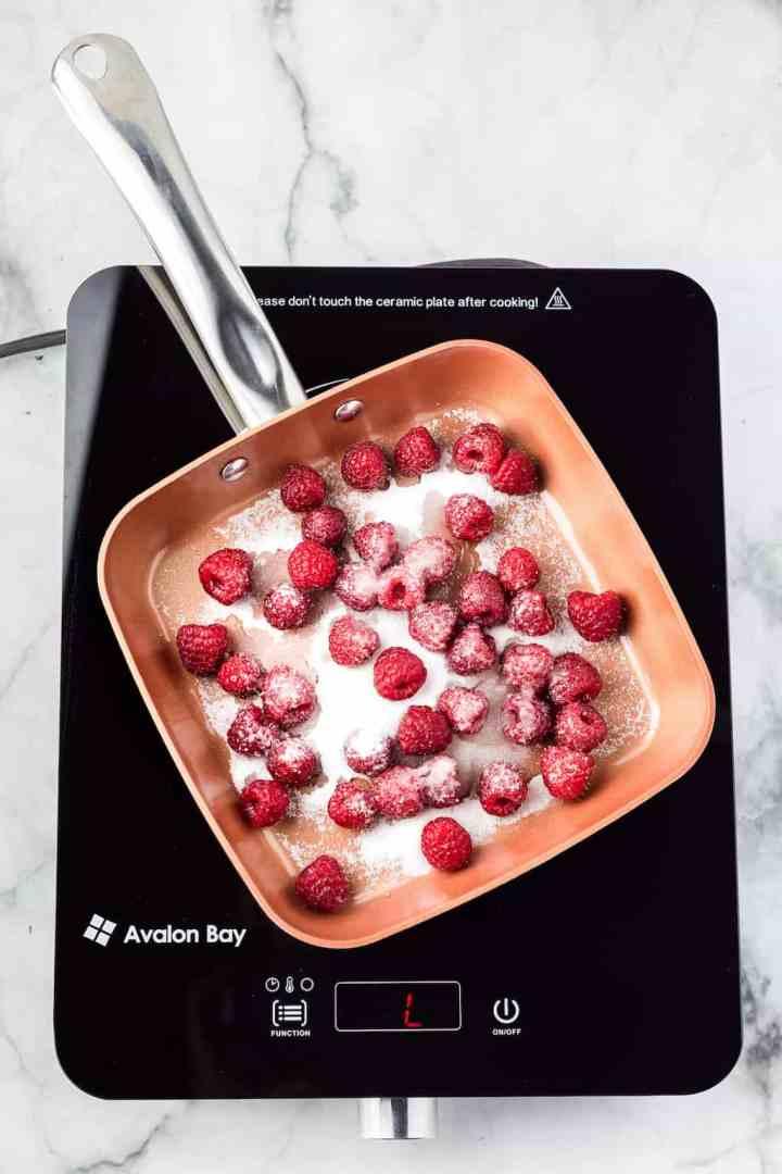 fresh raspberries and sugar in a copper skillet