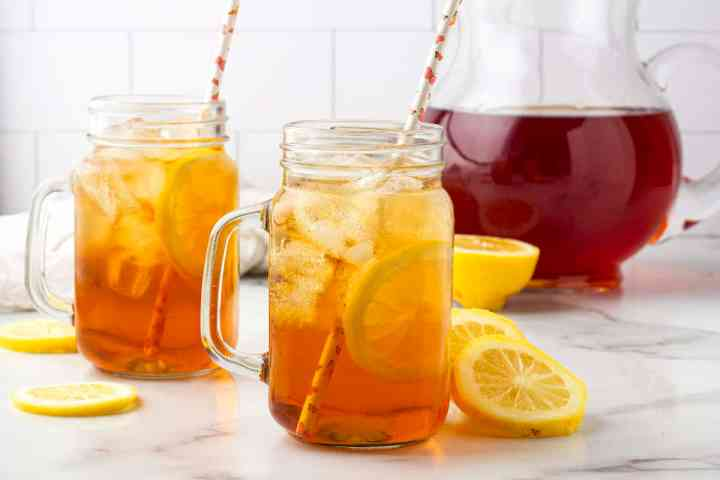 two glasses of southern sweet tea with a pitcher of iced tea