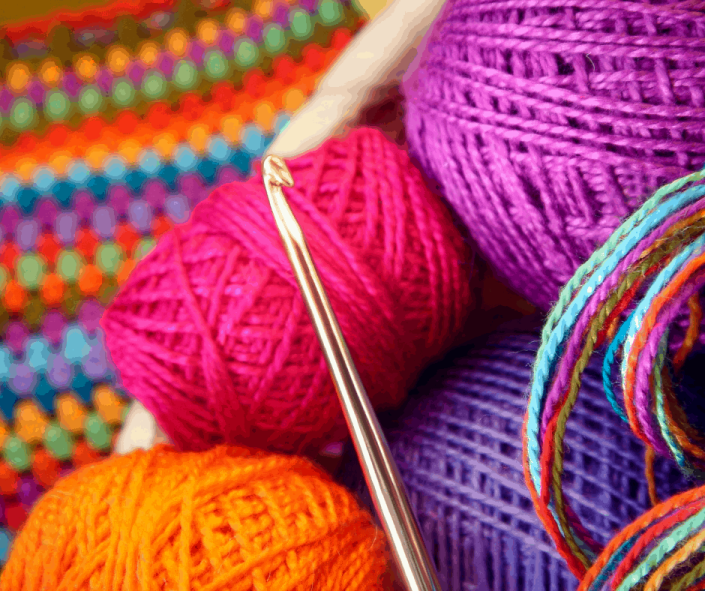 a crochet hook with brightly colored yarns and threads