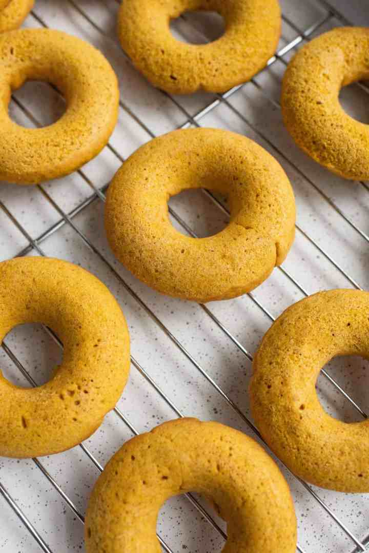 pumpkin spice donuts cooling on a wire rack