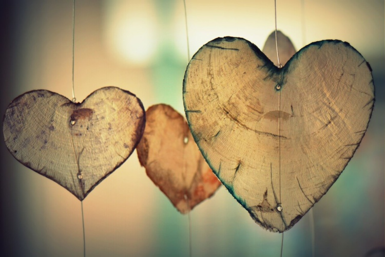3 Herzen aus geschnittenem Holz, nebeneinander aufgehängt an Drähten