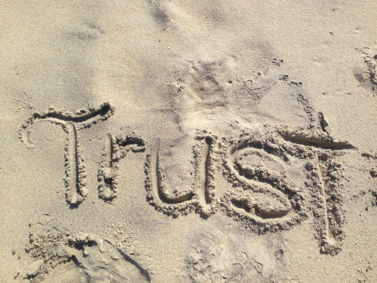 """In Sand geschriebenes Wort """"Trust"""""""