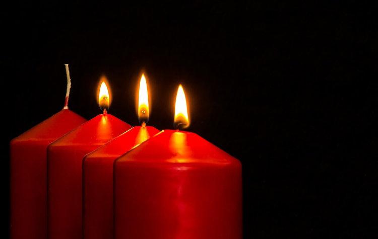 """3. Advent. Symbolbild """"Der lange Atem zum Warten"""". Nahaufnahme von vier roten Kerzen, 3 brennen."""