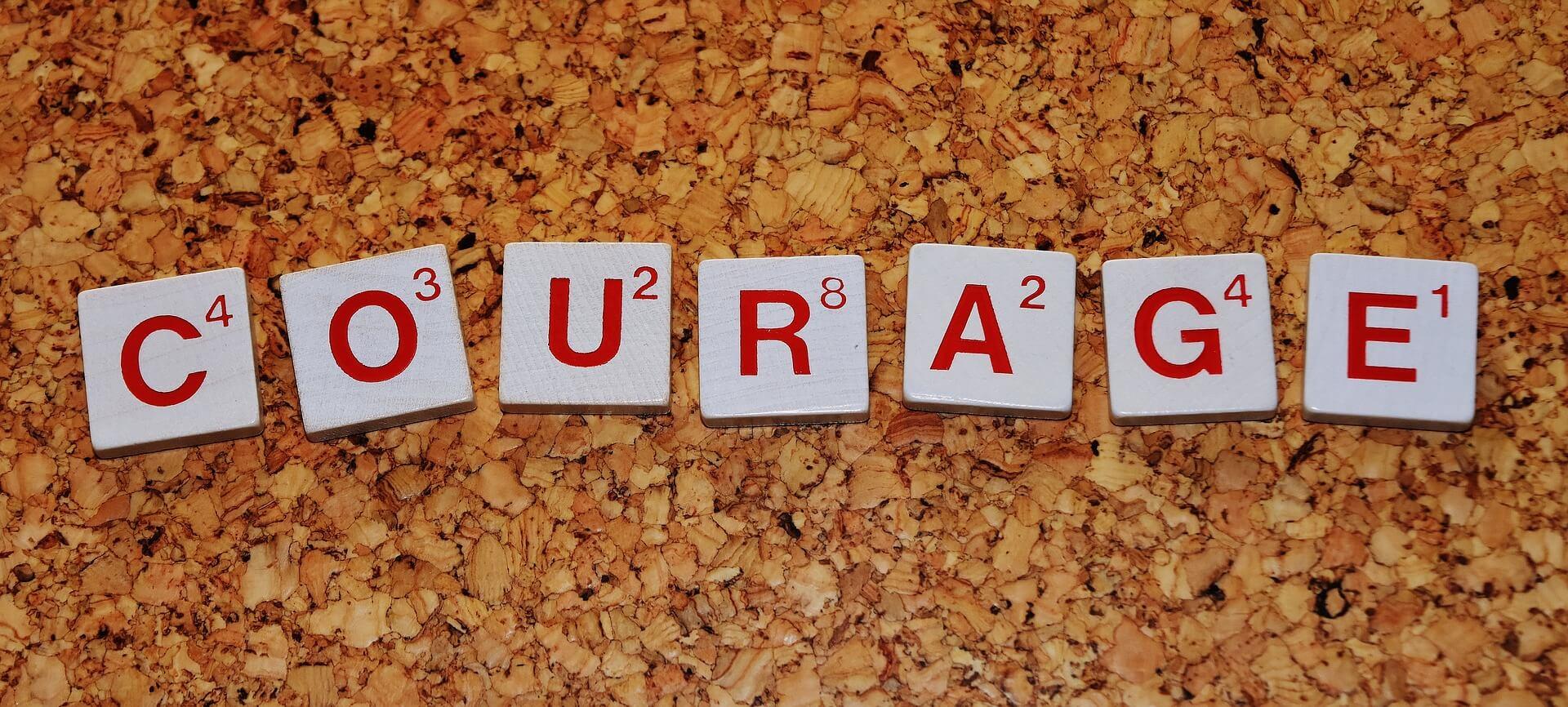 """Symbolbild: """"Kraft, Mut und Besonnenheit!"""": Englisches Wort Courage (übersetzt Kraft) mit Scrabble-Plättchen auf Steinen"""