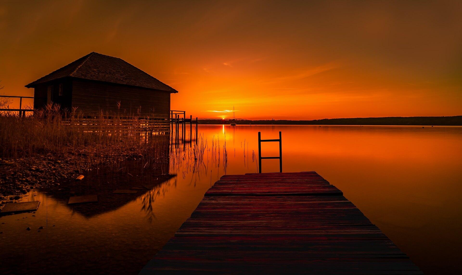 Im Abendrot des Glaubenslebens: Hütte und Steg bei Sonnenuntergang an einem See