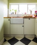 A checkerboard floor was created using simple plain tiles. Cream and charcoal create a softer look than black and white which worked better with the scheme.
