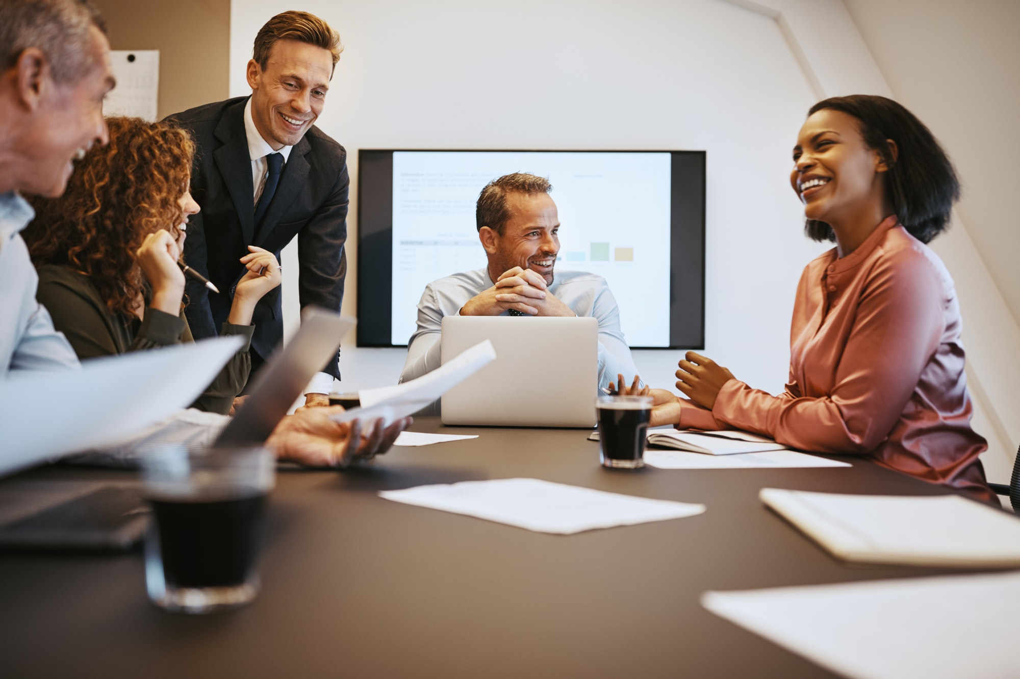 Group of smiling businesspeople discussing work together during a meeting