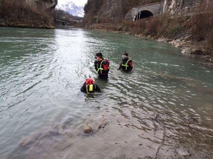3 Wildwasserretter suchen einen Gegenstand zur Bergung in der Ill