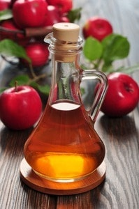 image of Apple cider vinegar in glass bottle and basket with fresh apples