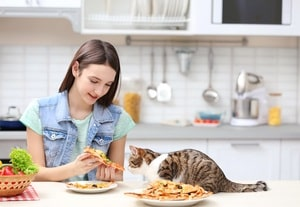 Young woman and cute cat eating tasty pizza in kitchen