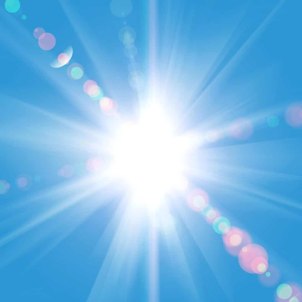 image of a Sun rays against a blue sky
