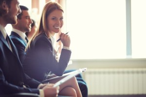 mujer-de-negocios-sonriente-con-un-boligrafo-en-una-conferencia_1098-561