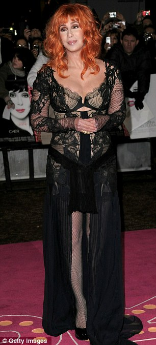 Revealing: Cher shows off her impressive figure in a black and nude Julien McDonald Autumn/Winter 2010 'mullet' lace gown at the London premiere of Burlesque