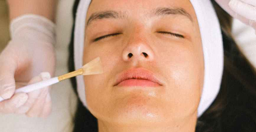 beautician putting cosmetic product on female client face