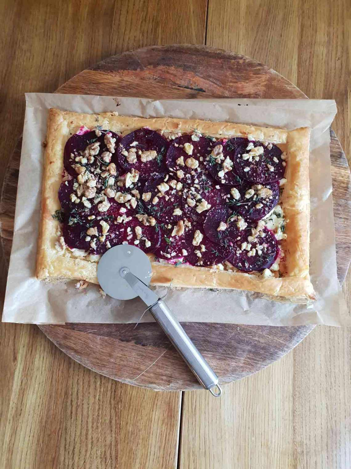 A beetroot and feta tart served on a round wooden board.