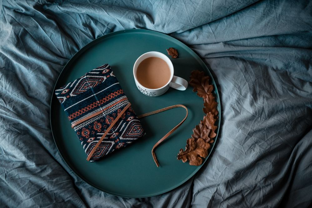 notebook and cup of tea on bed