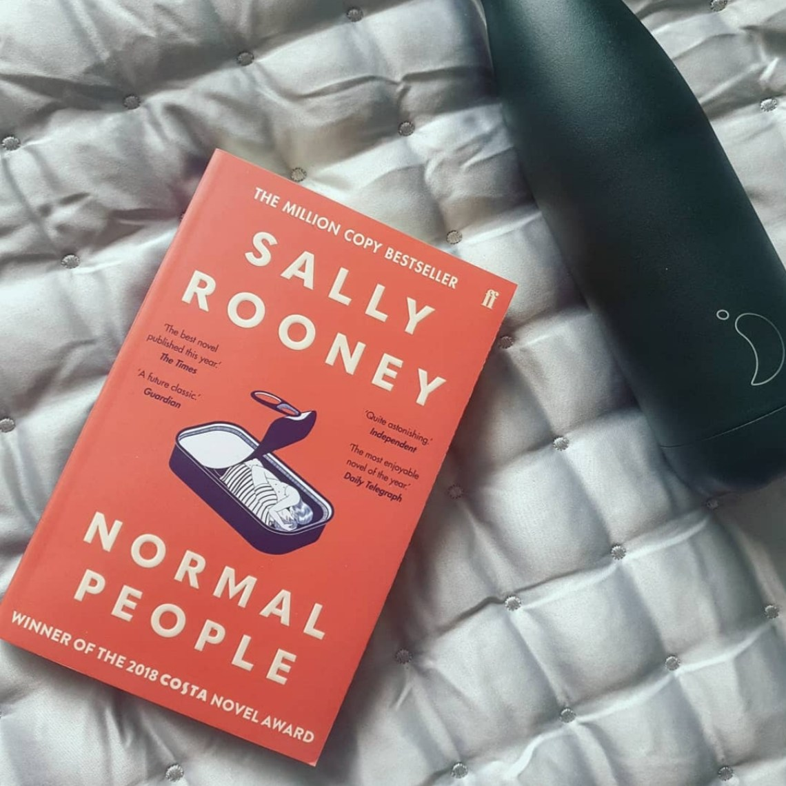A flatlay image of Normal People by Sally Rooney and a dark green Chilly's water bottle.