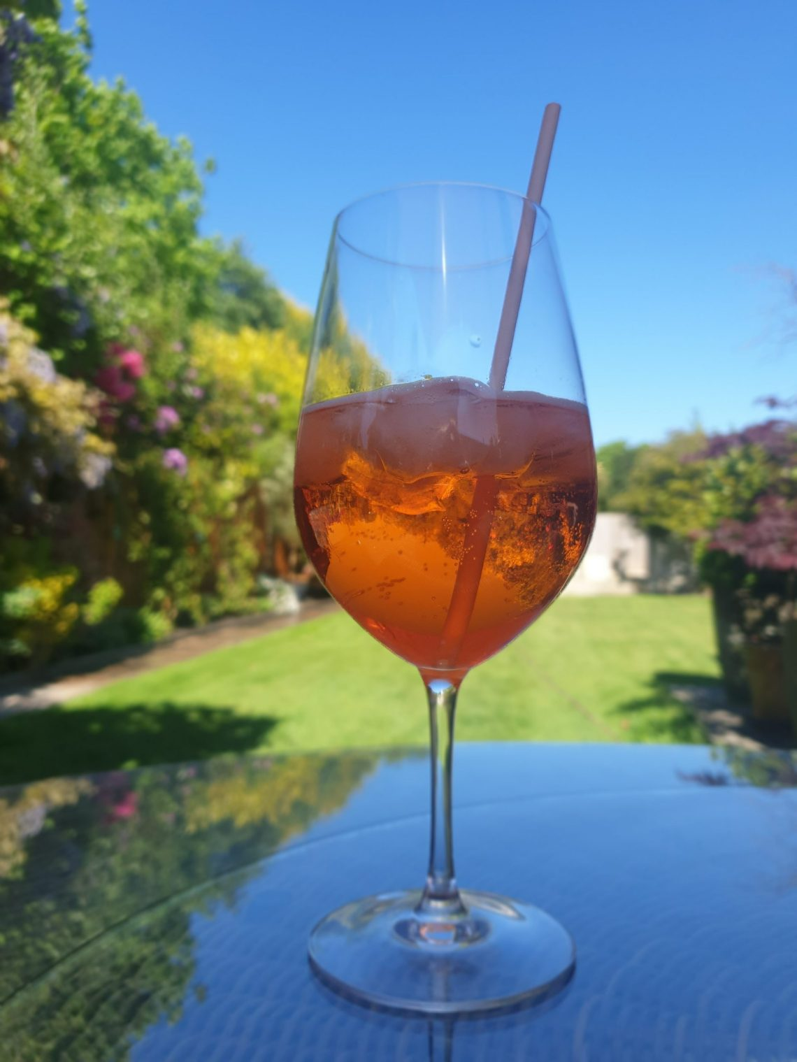 An Aperol Spritz cocktail with a garden scene in the background.