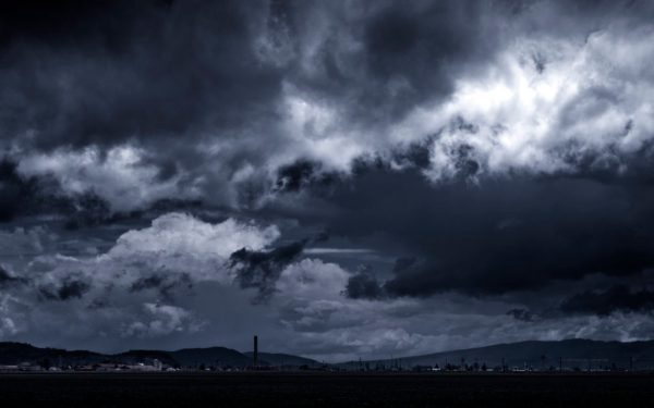 Storm Clouds Forming Over A Rural Village Wide Desktop Background