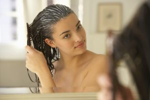 Young woman combing conditioner through hair, reflection in mirror