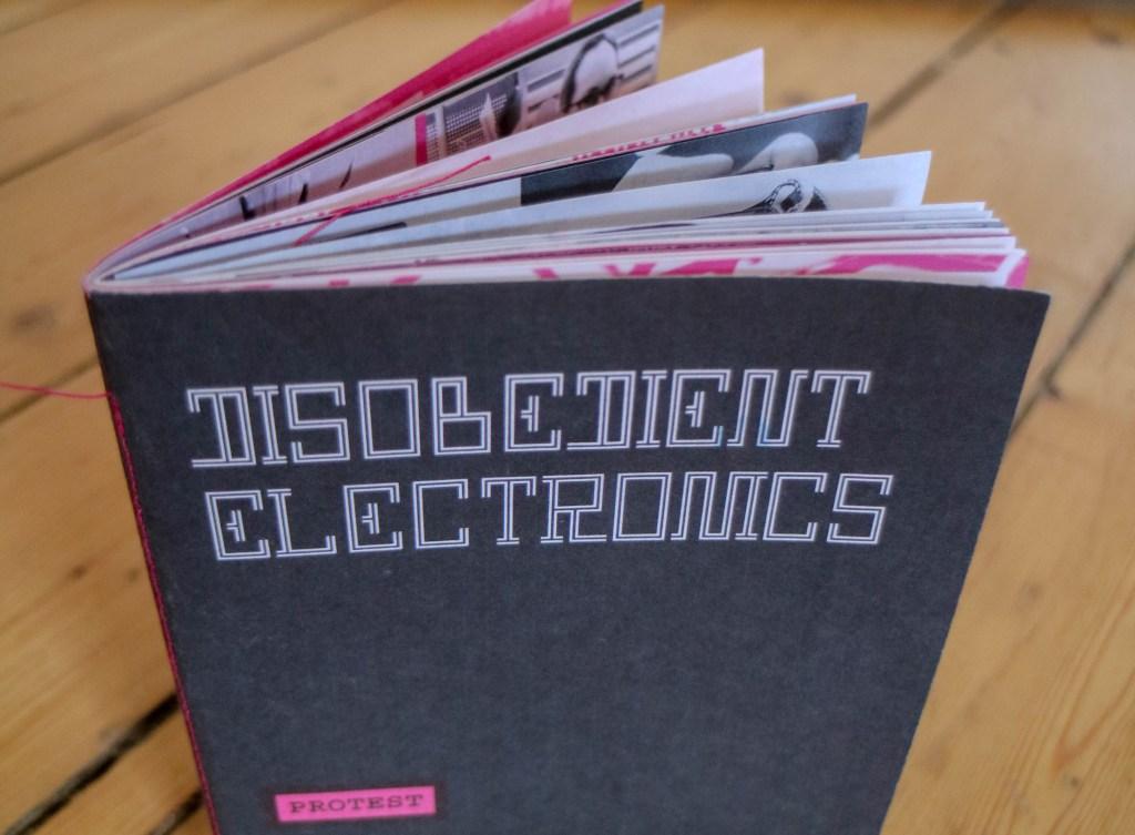 """Das aufgeblätterte, dunkle Zine """"Disobedient Electronics"""" auf Holzfußboden"""