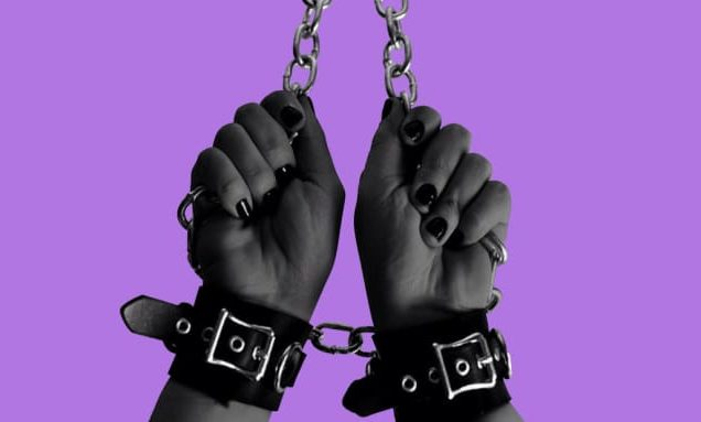 photo showing chained and cuffed hands with painted nails