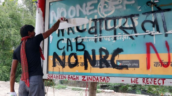 A man painting over protest graffiti at Shaheen Bagh in Delhi   Photo: Suraj Singh Bisht   ThePrint