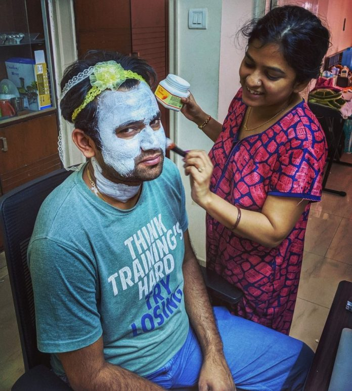 Women At Leisure: Sneha, helping her partner, Sourabh, put on a face mask. She put on their daughter's hair bands on his head to prevent his hair from falling on his face.