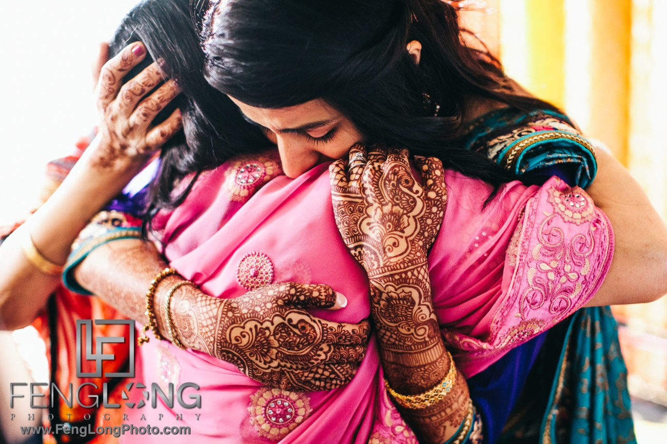 Indian bride hugging her mother and showing henna designs during ruhksati