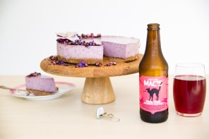 mac's sour puss beer next to a blueberry cheesecake on a wooden cake stand