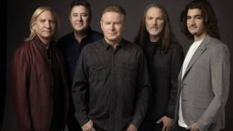 the eagles band members lined up against a black background
