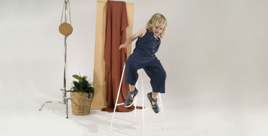 Bobux shoes worn by kid sitting on stool