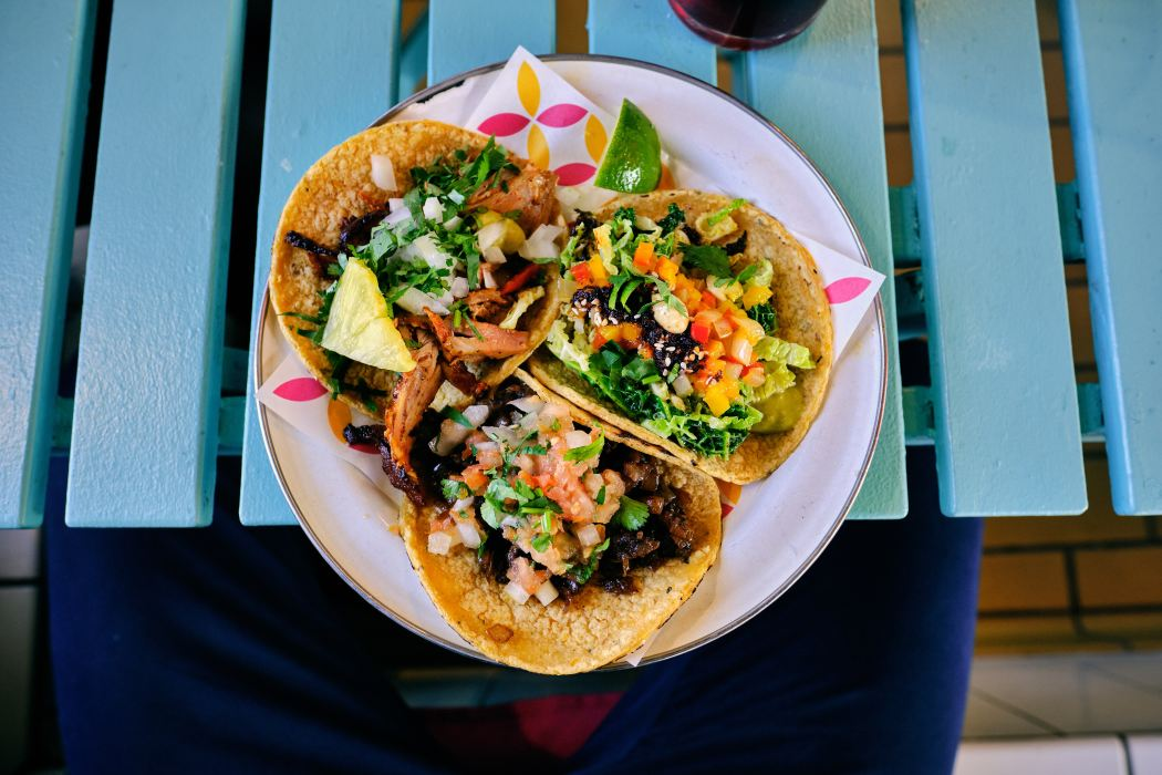 Three vegan tacos on blue wooden desk
