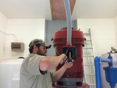 Dustin Schwartz wiring the red pump motor for the city of Pierre.