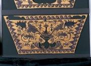 Το προικιό της νεκρής βασιλικής συζύγου συμπληρώνει ό,τι σώθηκε από το αριστοτεχνικά υφασμένο χρυσοπόρφυρο ύφασμα που σκέπασε τα οστά της και ένα χρυσό στεφάνι μυρτιάς, έργο σπουδαίου τεχνίτη που αποθανάτισε στο δημιούργημά του την πιο λαμπρή στιγμή της άνοιξης. Το ύφασμα ήταν υφασμένο με εξαιρετικά λεπτό νήμα από μαλλί βαμμένο με πορφύρα, την πιο πολύτιμη χρωστική της αρχαιότητας, και χρυσοκλωστή και αποτελεί εντελώς μοναδικό και απροσδόκητο τεκμήριο της εξαιρετικής ποιότητας της αρχαίας υφαντικής, μιας τέχνης που, λόγω της φύσης των υλικών της που διαλύονται και χάνονται στο πέρασμα του χρόνου, μας είναι ουσιαστικά άγνωστη.