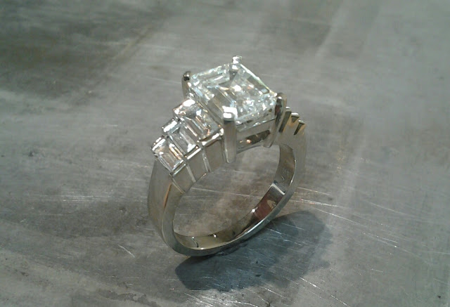 Square diamonds in large banded white gold engagement ring