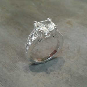 custom designed engagement ring featuring engraving and a princess cut diamond in a channel setting