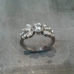 custom designed white gold engagement ring by sean ferguson with round cut diamond and diamond leaf accents
