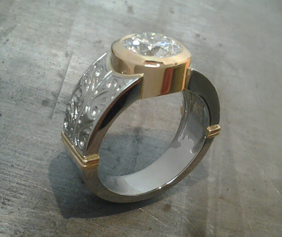 thick 14k gold and white gold engagement band with custom engraving and a round bezel set diamond side view