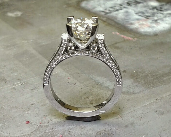custom designed engagement ring with band embellishments and a cathedral set diamond