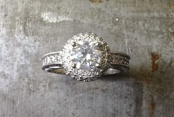 intricate engagement ring with custom engraved band with round diamond in a halo setting
