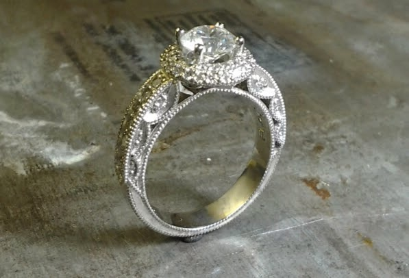 intricate engagement ring with custom engraved band with round diamond in a halo setting side view