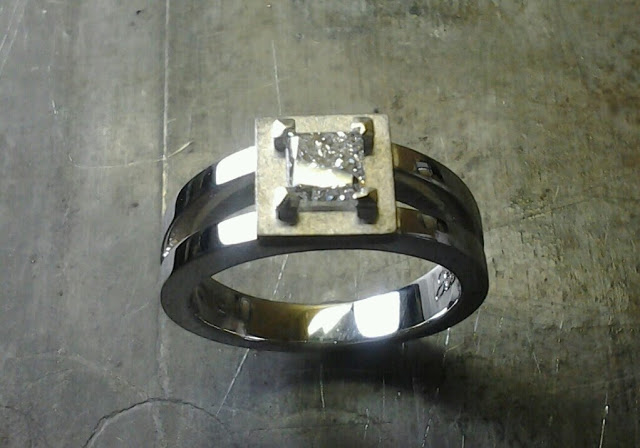 unique split white gold band with radiant diamond in a square setting