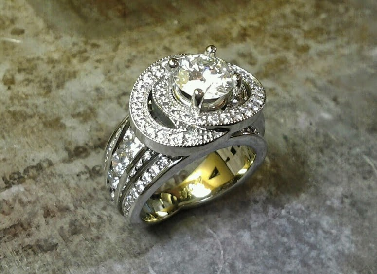 custom designed sphere ring with many diamonds in band and large round center diamond in halo setting