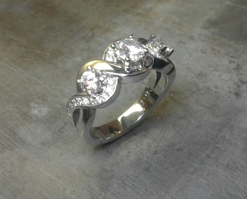 custom designed white gold engagement ring with swirled band and triple set diamonds side view