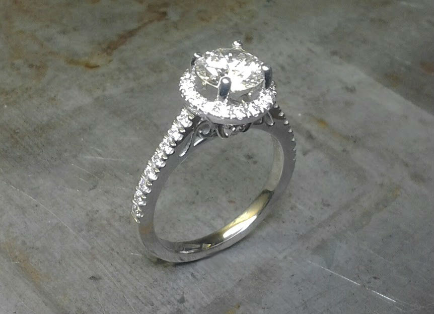 delicate white gold engagement ring with custom engraved band and large round center diamond