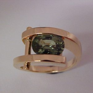 custom gold ring with tension set emerald