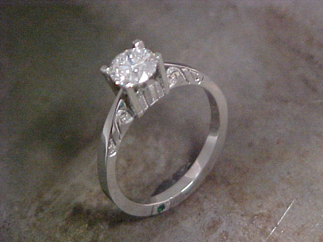 custom engagement ring with classic feel and small emerald in band